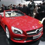 A worker removes fingerprints from the 2013 Mercedes Benz SL on the first press preview day at the North American International Auto Show in Detroit
