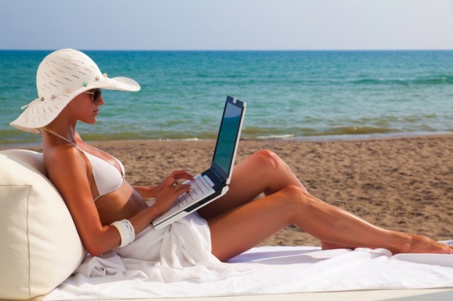 woman on beach working on  laptop against the sea