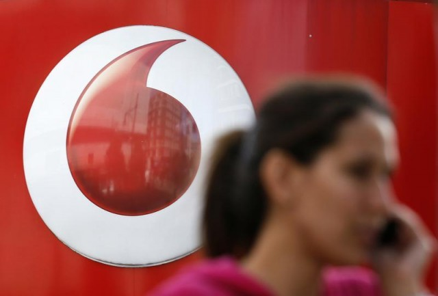 A woman talks on her mobile phone as she walks past a Vodafone store in London