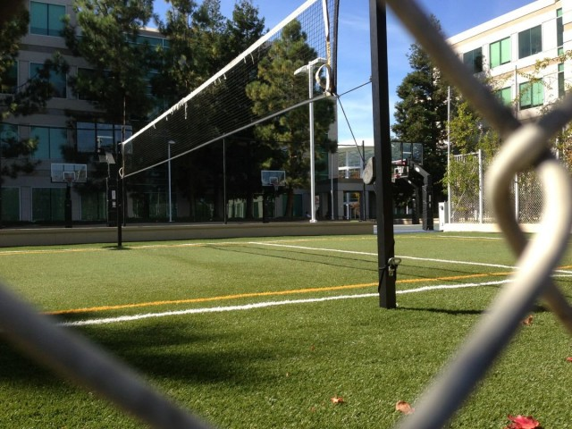 behind-the-chain-link-fence-is-a-volleyball-court-with-astroturf