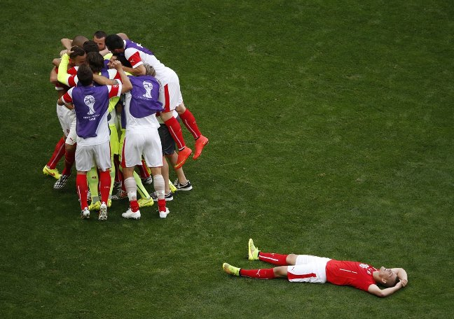 swiss-teammates-celebrate-as-midfielder-granit-xhaka-smiles-on-the-ground-exhausted