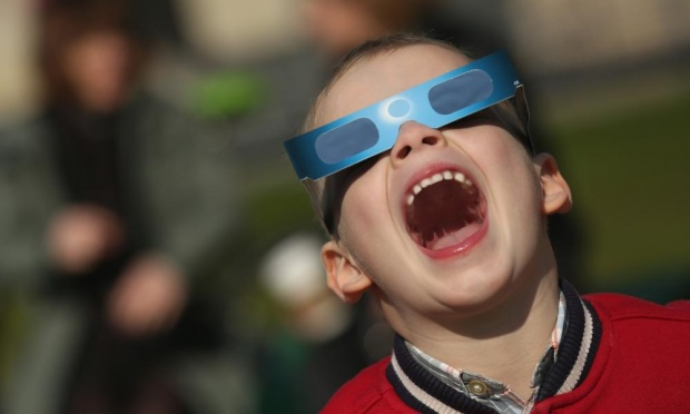 A German boy uses special glasses to look into the sky near the Brandenburg Gate in Berlin