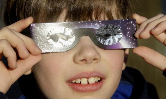 A boy looks at the sun through protective glasses in Berlin, Germany