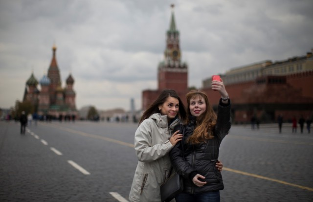 "FILE - In this Monday, Oct. 6, 2014 file photo, two young women pose for a selfie on Red Square with St. Basil's Cathedral, left, and the Spasskaya Tower, right in Moscow, Russia. Alarmed by the number of Russians who have been killed while taking photos of themselves with smartphones, Russian police have started a new campaign called ""Safe Selfies."" The instructions issued Tuesday, July 7, 2015 warn against standing on railroad tracks, climbing onto roofs or posing with a gun or a tiger. (AP Photo/Alexander Zemlianichenko, File)"