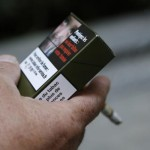 "A man smokes a cigarette on September 25, 2014 in Paris, holding a sample of a ""plain cigarette packaging"" cigarette box proposed by the ""Alliance contre le tabac"" (alliance against tobacco) association. France on September 25 said it would introduce plain cigarette packaging and ban electronic cigarettes in certain public places, in a bid to reduce high smoking rates among the under-16s. Following a successful similar campaign in Australia, Health Minister Marisol Touraine said cigarette packets would be ""the same shape, same size, same colour, same typeset"" to make smoking less attractive to young smokers.    AFP PHOTO THOMAS SAMSON        (Photo credit should read THOMAS SAMSON/AFP/Getty Images)"