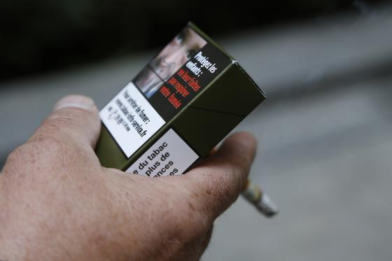 """A man smokes a cigarette on September 25, 2014 in Paris, holding a sample of a """"plain cigarette packaging"""" cigarette box proposed by the """"Alliance contre le tabac"""" (alliance against tobacco) association. France on September 25 said it would introduce plain cigarette packaging and ban electronic cigarettes in certain public places, in a bid to reduce high smoking rates among the under-16s. Following a successful similar campaign in Australia, Health Minister Marisol Touraine said cigarette packets would be """"the same shape, same size, same colour, same typeset"""" to make smoking less attractive to young smokers. AFP PHOTO THOMAS SAMSON (Photo credit should read THOMAS SAMSON/AFP/Getty Images)"""