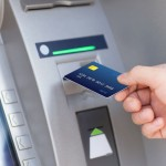 man hand puts credit card into ATM