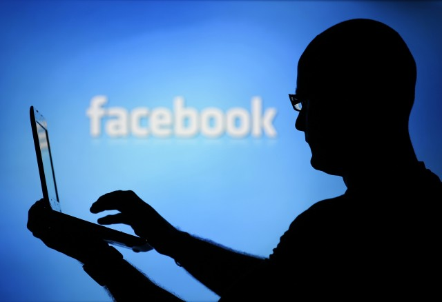 File photo of a man silhouetted against a video screen with an Facebook logo posing with an Dell laptop in this photo illustration taken in the central Bosnian town of Zenica