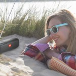 A young woman smiles as she listens to her retro style radio in the sand dunes on an idyllic beach.
