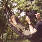 Relaxed man lying in hammock with digital tablet