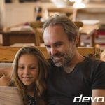 Father and daughter using laptop in living room
